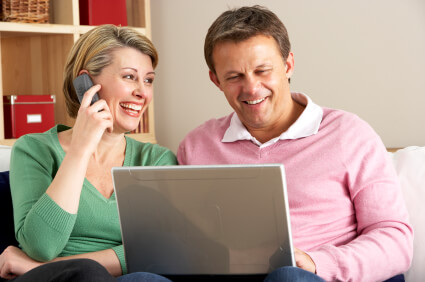 Middle-aged couple on the phone and computer